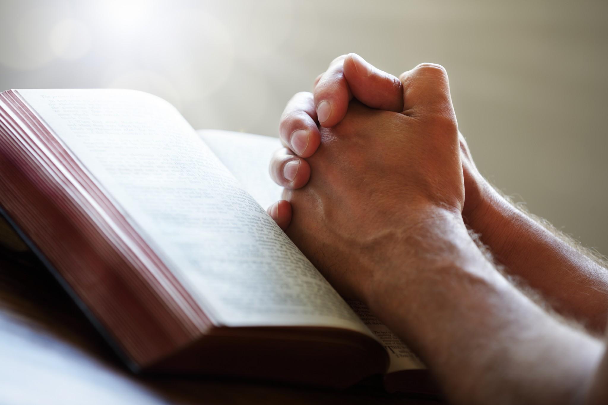 bigstock-Hands-folded-in-prayer-on-a-Ho-47921843